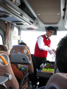 The bus attendant serving drinks - civilized bus travel.