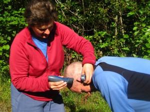 Becky giving Scott a haircut with Martin's battery-powered beard trimmer